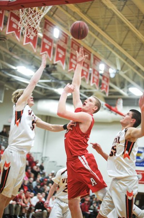 Austin's Joe Aase goes inside against a crowd of Winona players for two in the first half Tuesday night in Packer Gym. With the win the Packers clinched the Big Nine for the second straight year outright.