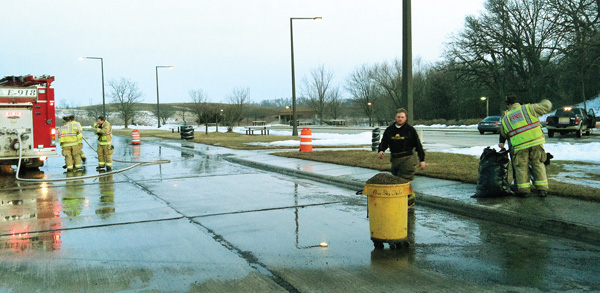 Albert Lea firefighters clean up an oil spill Friday evening at the Hayward rest area on Interstate 90. The firefighters trapped the oil, and state Department of Transportation crews disposed of the oil. Tim Engstrom/Albert Lea Tribune
