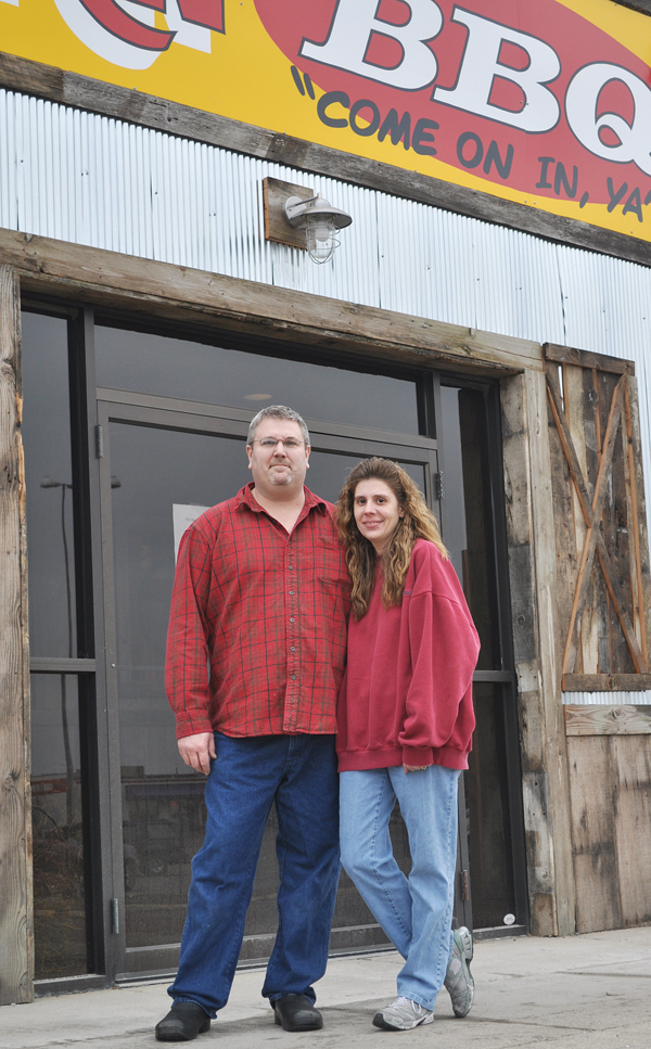 Bob and Lisa Nelson stand outside the Ole Barn BBQ restaurant in