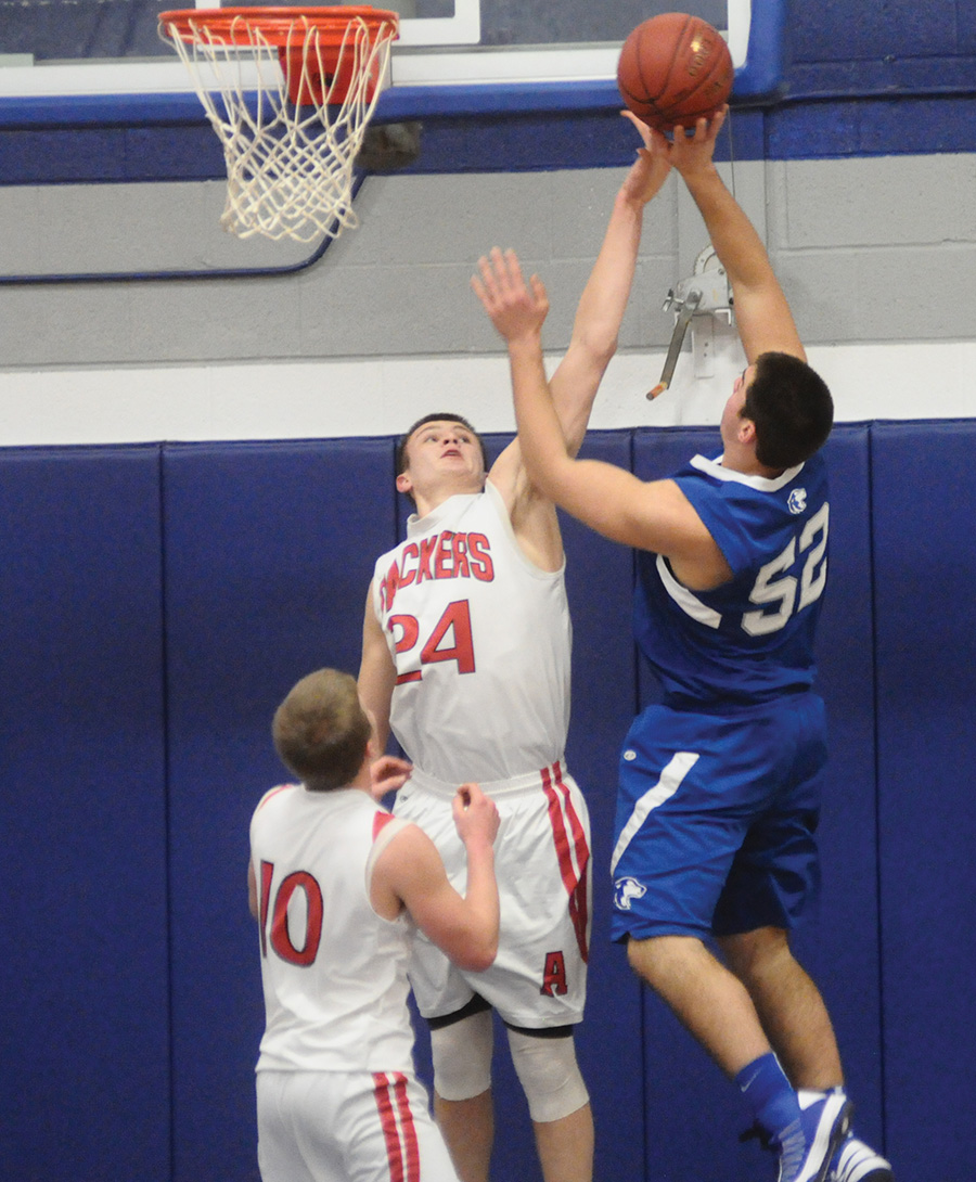 Austin's Tom Aase blocks the shot of Owatonna's Andrew Stelter during Friday's Big Nine Conference boys basketball game at Owatonna High School. -- Kyle Stevens/Owatonna People's Press