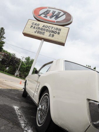 The A&W sign announces the upcoming car auction and hangs over 1966 Ford Mustang, one of the cars that will be auctioned off on June 29.