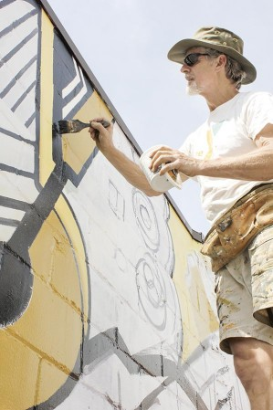Greg Wimmer of Rochester paints a section of a mural on the back side of Simplified Technology Solutions Monday morning in Austin. The mural is funded by the Main Street Project.
