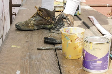 With splattered boots, Greg Wimmer stands on the scaffolding and makes progress on the newest mural in Austin