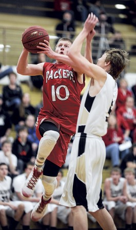 Austin's Bret Lukes heads to the hoop against the defense of Caledonia's Josh Nord during the first half Saturday night at Packer Gym. Eric Johnson/photodesk@austindailyherald.com