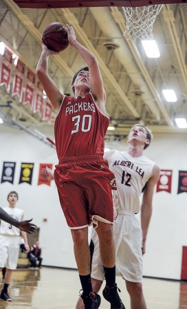 Austin's Noah Brehmer shoots in front of Albert Lea's Cody Scherff during the second half Friday night in Packer Gym. Eric Johnson/photodesk@austindailyherald.com