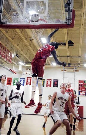 Austin's Gach Gach reaches back on an attempted dunk off a pass from Zach Wessels Friday night during the second half against Albert Lea. Gach just misssed on the dunk. Eric Johnson/photodesk@austindailyherald.com