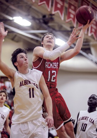 Austin's Zach Wessels' goes over Albert Lea's Tyler Vandenheuvel for two in the first half Friday night in Packer Gym. Wessels became Austin's all-time leading scorer after a pair of freethrows late in the second half. Eric Johnson/photodesk@austindailyherald.com