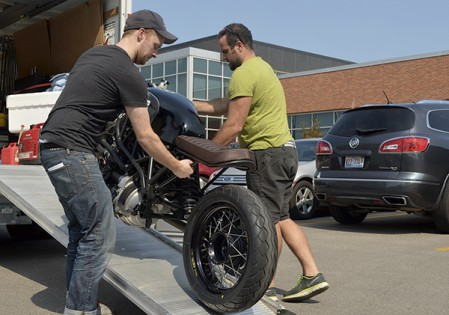 """Charlie Smithson, left, and Taylor Bamber remove Hormel Foods Corp.'s """"Driven By Bacon"""" motorcycle for a photoshoot in front of Hormel's offices in north Austin Monday. Photos by Trey Mewes/trey.mewes@austindailyherald.com"""