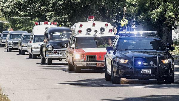 Austin police lead a caravan of old hearses, ambulances and limos toward the Mower County Fairgrounds Thursday.  Photos by Eric Johnson/photodesk@austindailyherald.com