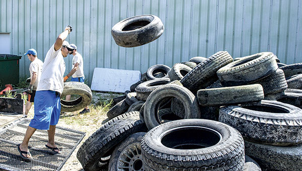Joe McCarthy of the Conservation Corps. Of Minnesota throws a tire on a pile Thursday afternoon. The group gathered the tires from the Cedar River.  Eric Johnson/photodesk@austindailyherald.com