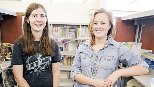 Sarah Schramek, left, and Kari Oanes are the chapter organizers of the Harry Potter Alliance. The group works to raise awareness. So far they hosted a book drive that received more than 400 books.  Eric Johnson/photodesk@austindailyherald.com