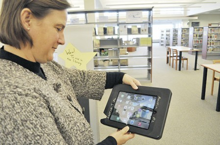 Ann Hokanson shows off one of the iPad Airs that is available to rent from the new self-serve machine at the Austin Public Library. The iPads come with apps pre-downloaded for users to use.