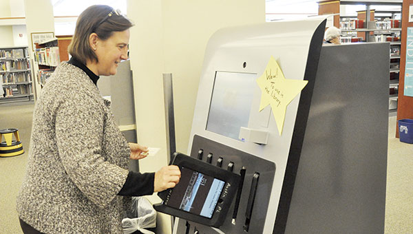 Ann Hokanson demonstrates renting an iPad Air from the self-serve machine at the Austin Public Library Monday. The library offers six iPad Airs and six HP 14-inch laptops for rent to library-card holders for four hours at a time. Jenae Hackensmith/jenae.thackensmith@austindailyherald.com