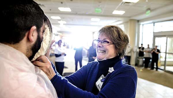 Karen Morlan steps up and gives Matt Unverzagt a face-full of pie Wednesday at Mayo Clinic Health System — Austin. The event was held as a celebration for departments making goal in a fundraising campaign for the United Way. -- Eric Johnson/photodesk@austindailyherald.com