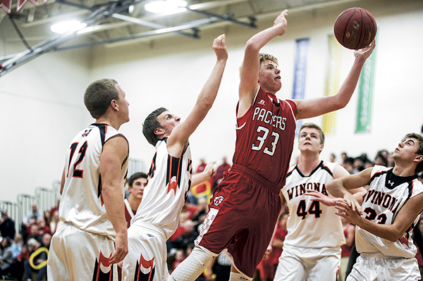 Austin's Kyle Oberbrockling puts up a shot off the rebound during the first half against Winona Tuesday night in Packer Gym. Eric Johnson/photodesk@austindailyherald.com