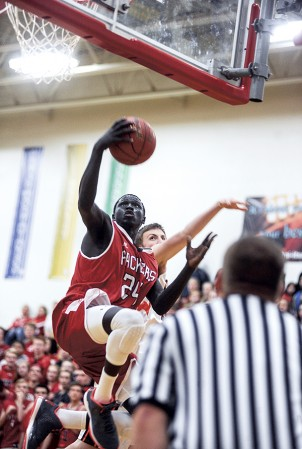 Austin's Gach Gach goes in for two of his 17 first-half points against Winona Tuesday night in Packer Gym. Eric Johnson/photodesk@austindailyherald.com