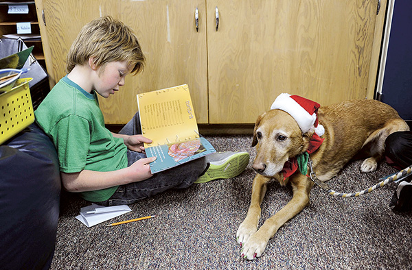 Southgate third-grader Gavyn Skattebo reads as Penny, a golden retriever mix belonging to Jan Haycraft, listens Friday morning. Eric Johnson/photodesk@austindailyherald.com