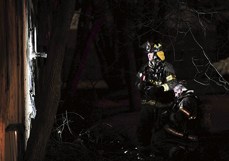 Austin firefighters look for hotspots on the outside of a room at the Sterling Motel Tuesday night.