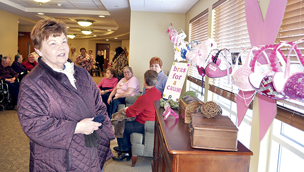 Patti Bayley examines several paper bras at the Bras for a Cause contest Wednesday at St. Marks Living. -- Photos by Trey Mewes/trey.mewes@austindailyherald.com