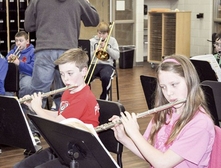 Austin Pelletier and Piper Kellner play flutes as one section of the fifth-grade band at I.J. Holton plays Old McDonald Friday morning in the band room. Director Tim Davis had the students clap the melody first, and then play the notes before playing the song. Jenae Hackensmith/jenae.hackensmith@austindailyherald.com
