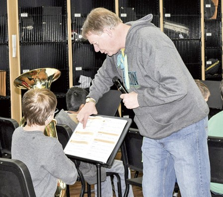 Director Tim Davis points out a place in Carter Gilster's music book as one section of the fifth-grade band at I.J. Holton plays Old McDonald Friday morning in the band room. Davis had the students clap the melody first, and then play the notes before playing the song. Jenae Hackensmith/jenae.hackensmith@austindailyherald.com