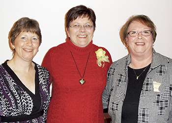 Mary Jo Follmuth (Birtch Travel), Gina Grundmeier, and Cheryl Retterath stand at the Zonta Woman of Achievement Banquet.