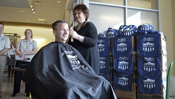"""Jeff Baker, vice president of marketing, food service, for Hormel Foods Corp., smiles as he gets a """"high and tight"""" haircut Friday as part of a fundraising effort for homeless veterans. Baker and other members of Hormel's Military Veterans Engagement Team (HMVET) recently donated more than 700 bags filled with hygenic products to the Minnesota Area Council for Veterans to help Minnesota's homeless vets. Trey Mewes/trey.mewes@austindailyherald.com"""