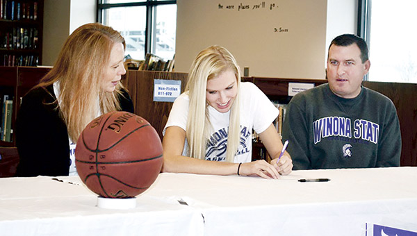 John Worke, right, watched his daughter Madison sign her national-letter-of-intent to Winona State in 2014. Worke is stepping down as head girls basketball coach at Blooming Prairie after 22 years on the job. Herald File Photo