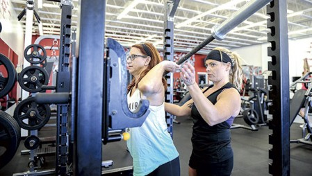 Jennifer Jenkins helps Kristin Aakre during a personal workout at Total Fitness, owned by Jenkins.