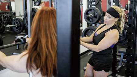 Jennifer Jenkins, owner of Total Fitness, works with Kristin Aakre during an invitational workout.