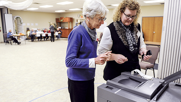 Sara Schafer-Perkins, right, and Linda Baumann begin printing 2014 election results after voting closed at the Mower County Senior Center. Minnesota Secretary of State Steve Simon is calling for the state to update its voting equipment. -- Herald file photo