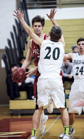 Zach Coffey tries to pass around Faribault's Ramsey Shaffer during the first half Tuesday night along the baseline in Packer Gym. Eric Johnson/photodesk@austindailyherald.com