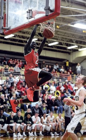Austin's Duoth Gach puts down a big, two-handed dunk following a steal against Rochester Mayo in Packer Gym Friday night. Eric Johnson/photodesk@austindailyherald.com