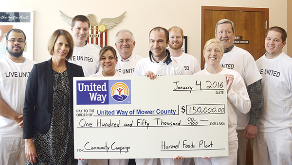 United Way of Mower County Executive Director Diane Baker accepts a check for $150,000 from the Hormel Foods Corp. plant workeres Monday in the plant lobby.  -- Jenae Hackensmith/jenae.hackensmith@austindailyherald.com