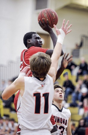 Oman Oman drifts a shot against Winona's Jonah Boelter during the second half Tuesday night in Packer Gym. Eric Johnson/photodesk@austindailyherald.com