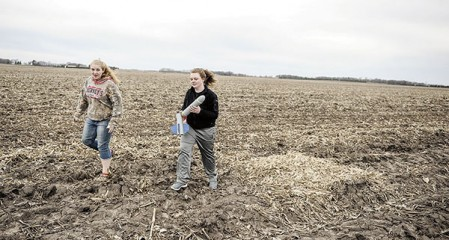 Leah Meineke, right, and Christine Nelson trudge across a field after retrieving the rocket.