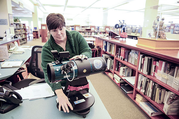Library assistant Kris Olson sets out one of two telescopes at the Austin Public Library. Eric Johnson/photodesk@austindailyherald.com