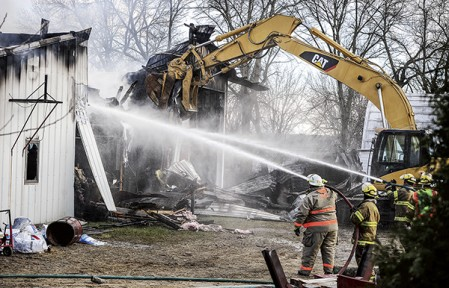An excavator pulls away a portion of a wall as firefighters put water on a bodyshop in Grand Meadow Friday afternoon. Eric Johnson/photodesk@austindailyherald.com
