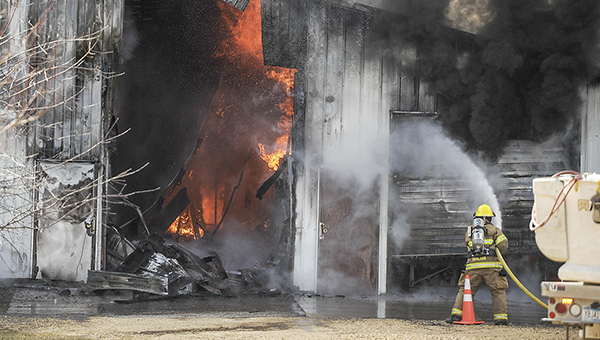 Flames rage inside a body shop as a firefighter puts water on the building in Grand Meadow Friday afternoon. Eric Johnson/photodesk@austindailyherald.com