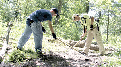 Southern Minnesota Bike Club co-President Pat Edwards, left, and Gareth Hataye work on a portion of the Austin mountain biking trail Saturday during a visit by the International Mountain Bicycling Association's Subaru/IMBA Trail Care Crew.   Jason Schoonover/jason.schoonover@austindailyherald.com