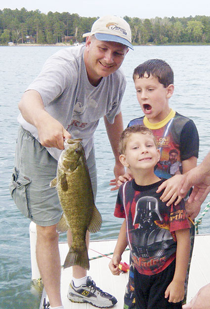 "Lawhead's son Will won the family fishing contest with this nice smallmouth bass. His older brother, Brock, who expected to win the contest, was shocked by the catch. Lawhead was able to fish with Don ""Hootch"" Hanson, an Austin graduate who started his own tackle shop called The White Whale known for making his own rods and selling quality tackle. Photo provided"