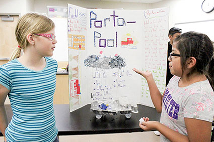 Grace Purrier, 10, left, and Maria Ruiz, 10, present their group project. E3 is a summer education initiative for students from Austin, Albert Lea, Hayfield, Lyle and Southland school districts