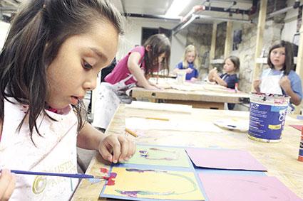 Sarah Gonzalez, 6, paints a portrait of herself during the week long Kids Art History Camp.  Jora Bothun/jora.bothun@austindailyherald.com