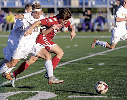 Austin's Matias Parada battles with Rochester Lourdes' Joe Novak during the first half of the Section 1A title game last October in Rochester.  Herald file photo