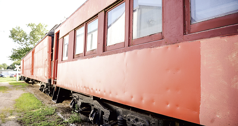 A quick coat of paint is applied to one of the train cars that was vandalized earlier this week. -- Eric Johnson/photodesk@austindailyherald.com