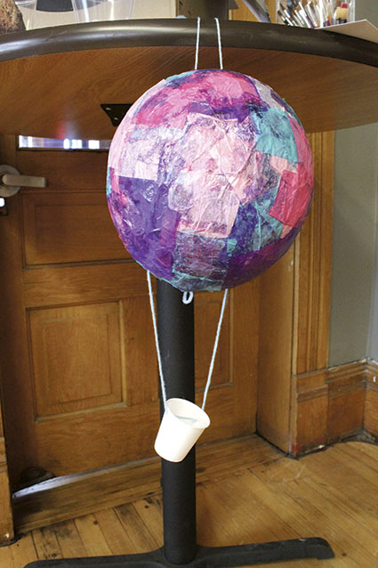 A kid's tissue paper balloon dries while it hangs from a table.