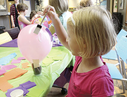 Signe Oftley works on her tissue paper balloon.
