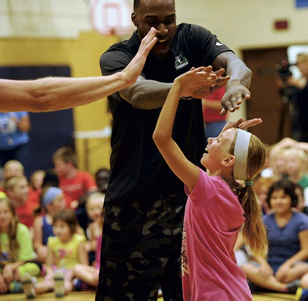 Katie Rauen, a 10-year old from Austin, high fives Shabazz Muhammed of the Minnesota Timberwolves at the Caravan in the Austin YMCA Monday. Rocky Hulne/sports@austindailyherald.com