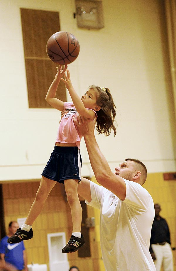 Cole Aldrich of the Minnesota Timberwolves hoists up Alana Tria, a 6-year old from Austin, as she attempts a shot in the Timberwolves Caravan in the YMCA Monday. Rocky Hulne/sports@austindailyherald.com