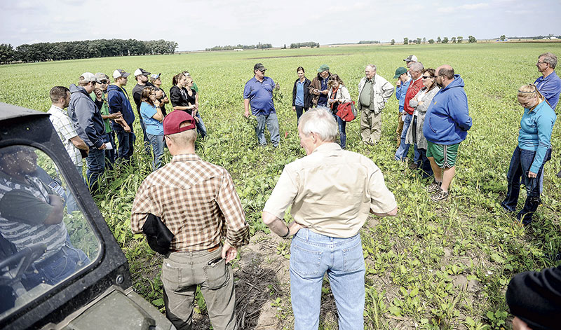 TJ Kartes of Saddle Butte Ag Inc. talks to a tour group about the benefits of cover crops on a field belonging to Tom Cotter Thursday afternoon. Eric Johnson/photodesk@austindailyherald.com